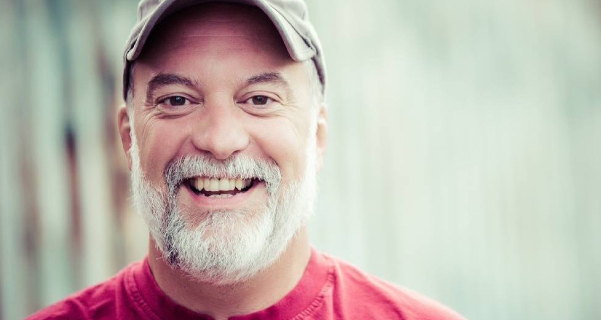 Tightly framed head shot of author Greg Brisendine smiling at the camera. Author is wearing a neutral-colored baseball cap and a red shirt and is standing against a blurry, neutral background.